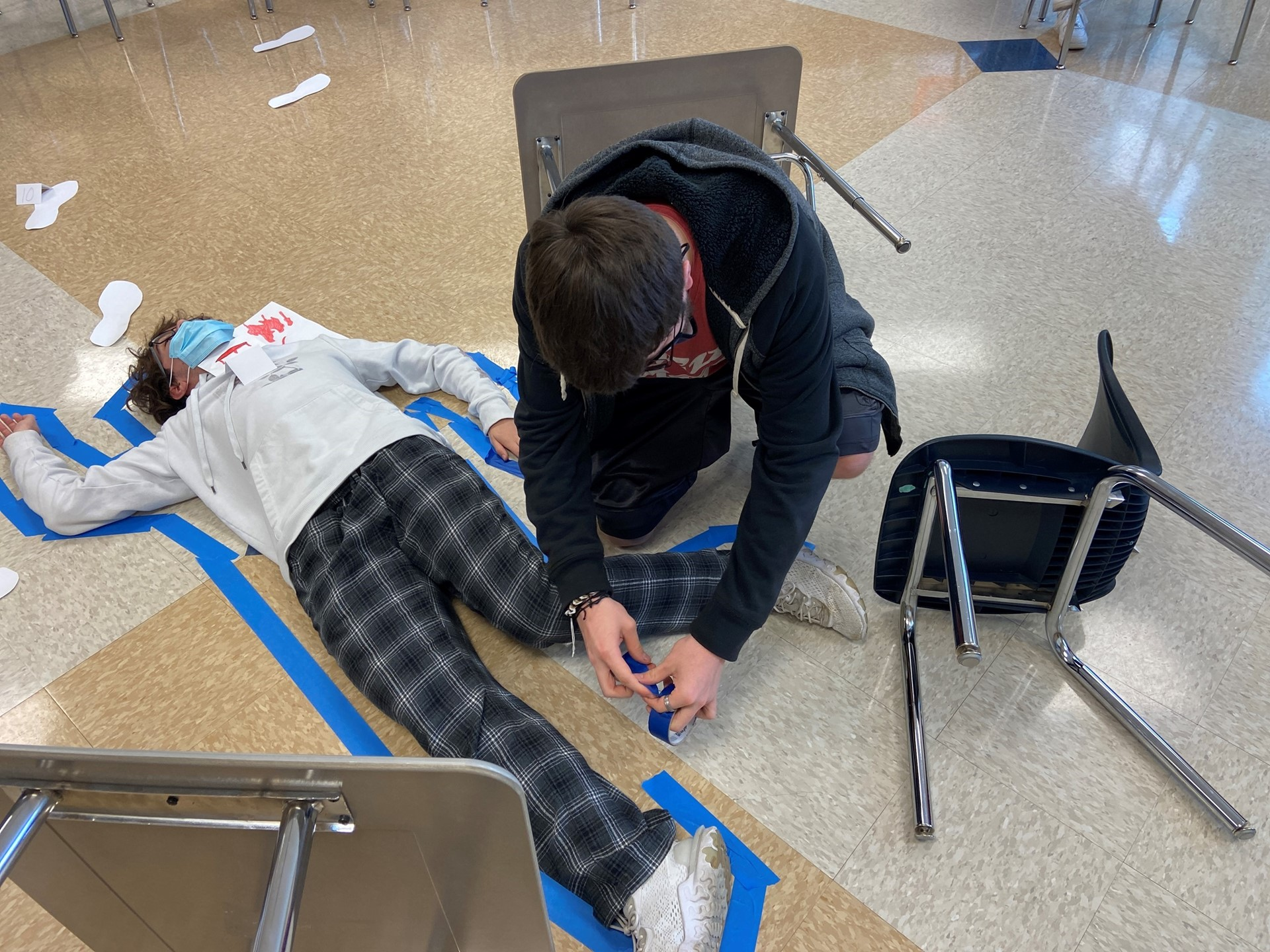 Students create a tape outline of a person in class.