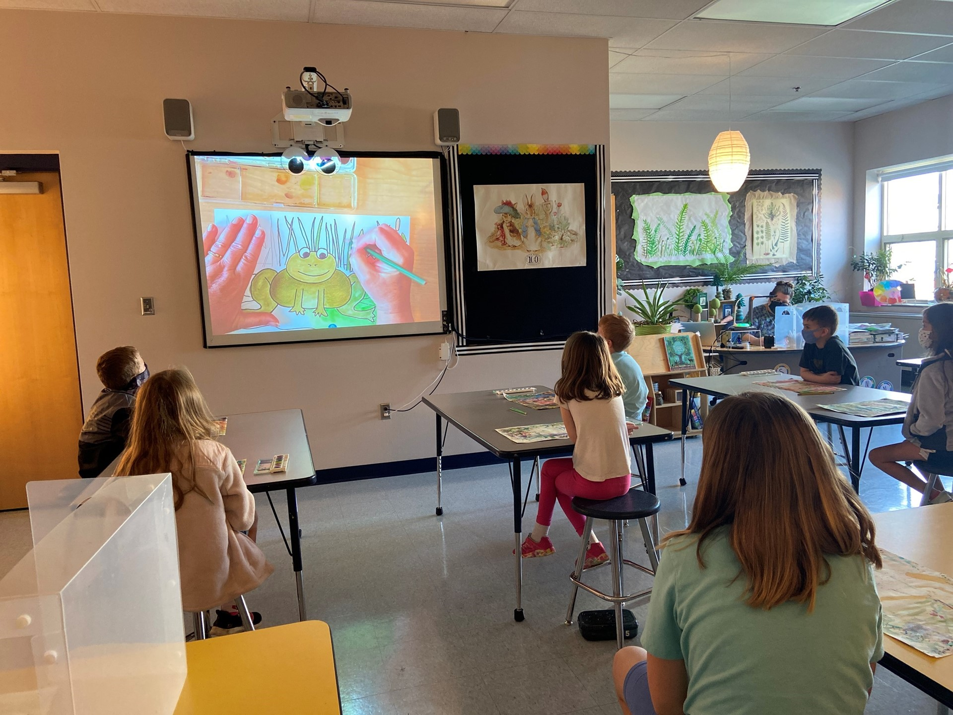 Students in art class observing the teacher draw a frog.