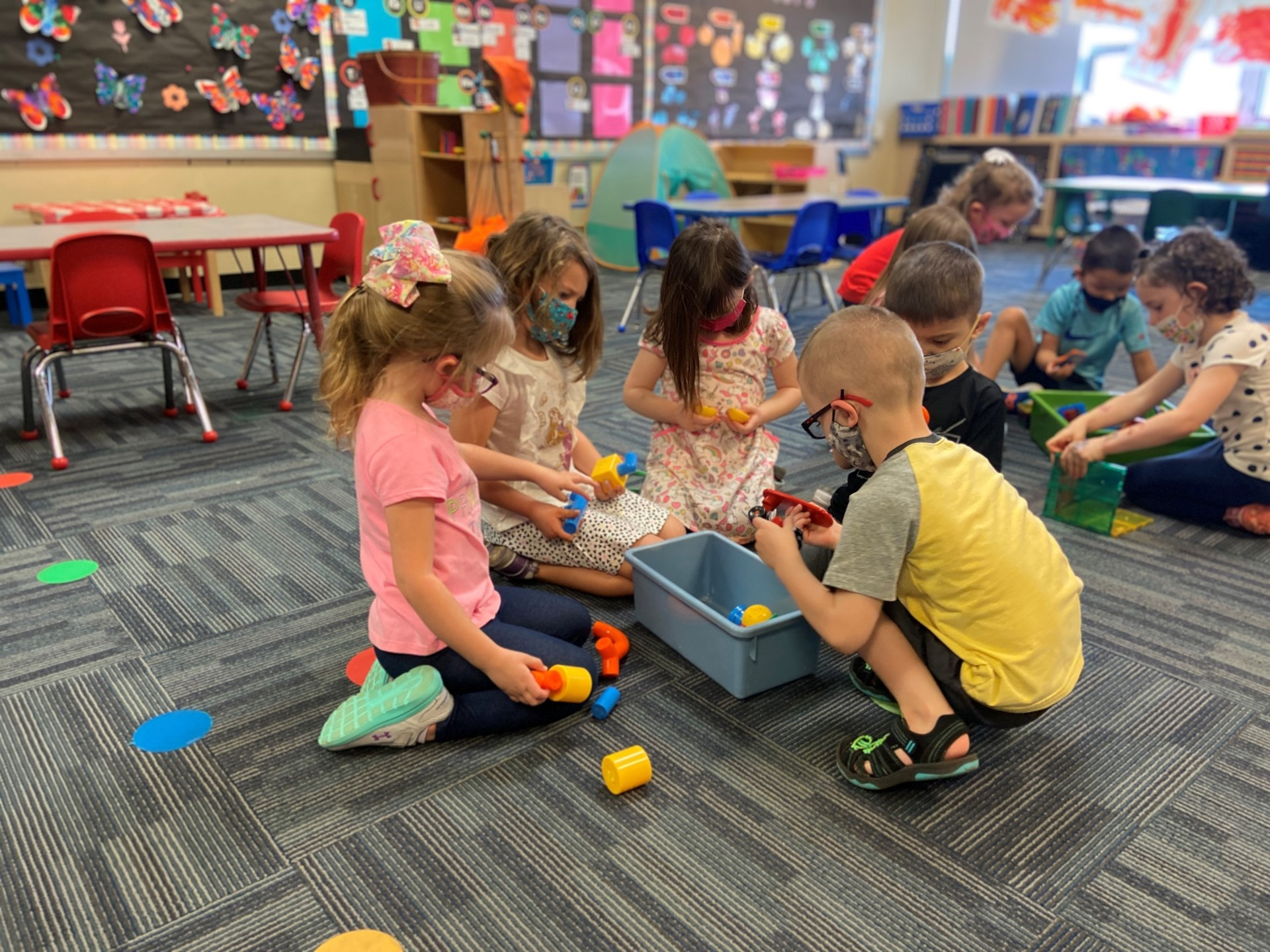 Students play with manipulatives in a group.