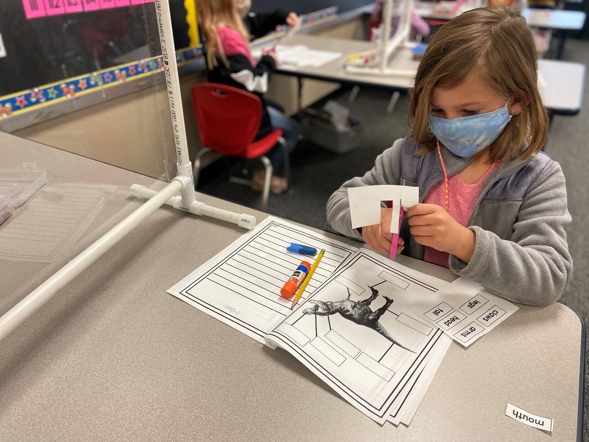 A student works to cut out labels for the dinosaur.