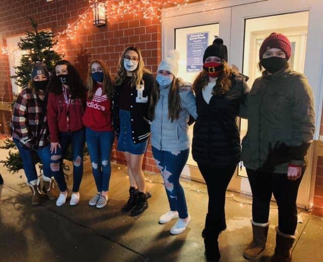Students pose at an outdoor Christmas caroling event.